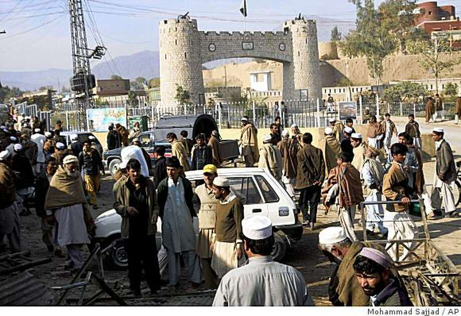 Pakistani tribal people gather at Khyber pass, a road to neighboring Afghanistan, after its reopening near Peshawar, Pakistan, on Friday, Jan. 2, 2008. Pakistan reopened the main supply route for U.S. and NATO troops in Afghanistan on Friday after blocking it for three days during a military operation against militants who have been attacking supply convoys. (AP Photo/Mohammad Sajjad) Photo: Mohammad Sajjad, AP