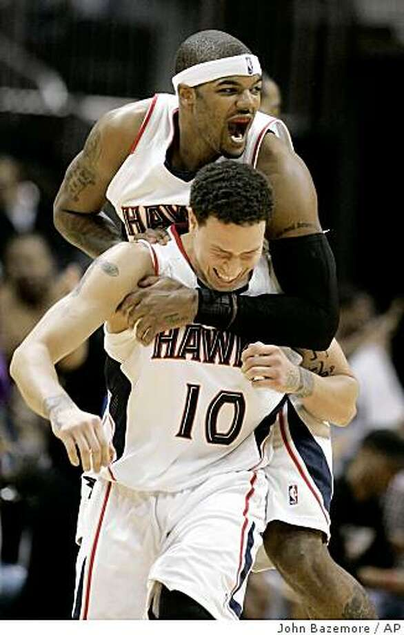 Atlanta Hawks' Mike Bibby (10) celebrates with teammate Josh Smith after hitting a 3-point basket in the fourth quarter of an NBA basketball game against the Denver Nuggets in Atlanta on Monday, Dec. 29, 2008, in Atlanta. Atlanta won 109-91. (AP Photo/John Bazemore) Photo: John Bazemore, AP