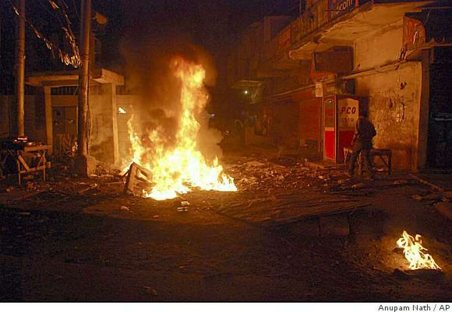 A fire burns after a blast in the Bhangagarh area of Gauhati, India, Thursday, Jan. 1, 2009. Three bombs exploded in India's restive northeast Thursday, killing at least five people and wounding 50, about an hour before the nation's top security official arrived in the area.( AP Photo/Anupam Nath) Photo: Anupam Nath, AP