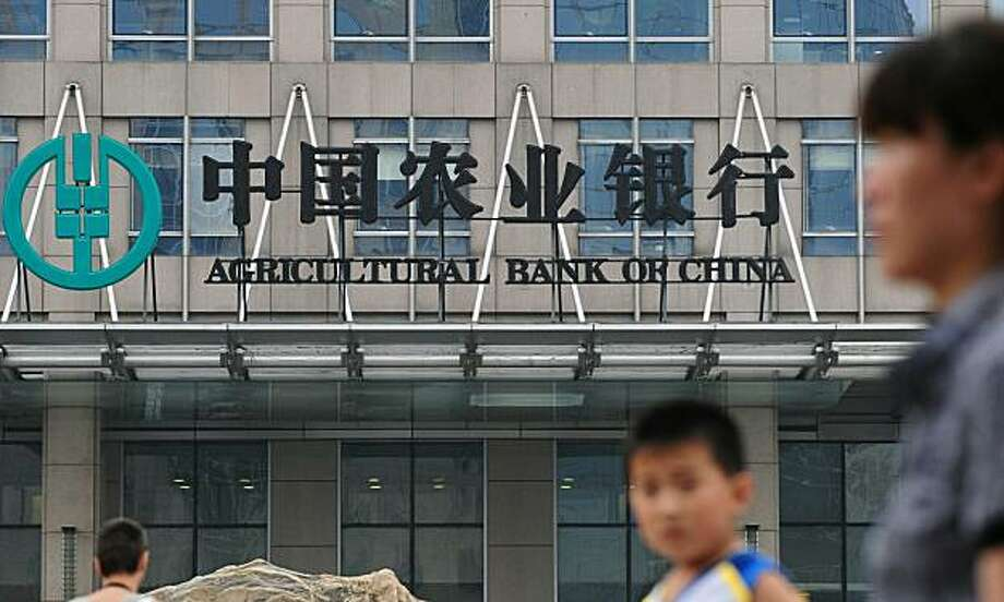(FILES) In a file picture on July 14, 2010 pedestrians walk past the headquarters of the Agricultural Bank of China in Beijing. Agricultural Bank of China has claimed the title of the world's largest initial public offering after fully exercising the over-allotment option of its Shanghai share offering, Dow Jones Newswires said on August 14. Photo: Frederic J. Brown, AFP/Getty Images