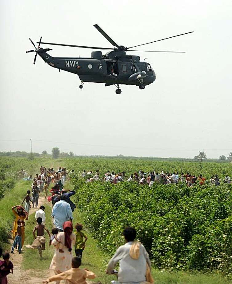 Pakistani flood survivors rush towards a navy helicopter distributing food bags in Khairpur district on August 12, 2010. Water levels receded in Pakistan on August 12 but survivors of record floods endured grim conditions in makeshift tent cities, as theUN appealed for 460 million dollars in urgent foreign aid. Pakistan's government says 14 million people face direct or indirect harm from the floods. The United Nations believes 1,600 people have died in the floods, while Pakistan has confirmed 1,243 deaths. Photo: Aamir Qureshi, AFP/Getty Images