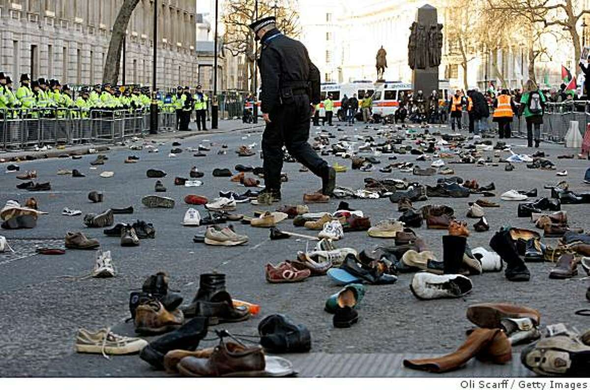 LONDON - JANUARY 3: A policeman walks through the shoes thrown by demonstrators onto the street in front of the entrance to Downing Street in protest against the continued aerial bombardment of Gaza by Israel on January 3, 2009 in London, England. Israel has so far carried out over 700 air strikes in Gaza within the last week and over 400 Palestinians are reported to have been killed. (Photo by Oli Scarff/Getty Images)