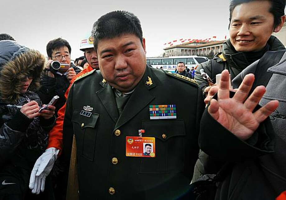 (FILES) This file picture taken on March 5, 2010 shows Mao Xinyu (C), grandson of late Chinese leader Mao Zedong, talking to the media outside the Great Hall of the People after the opening session of the annual National People's Congress (NPC) in Beijing. Mao, a 40-year-old politician and researcher at the Academy of Military Sciences of the People's Liberation Army, was promoted to major general in the nation's army ahead of the 83rd anniversary of the PLA's founding on August 1, state media said on August 2, 2010. Photo: Goh Chai Hin, AFP/Getty Images