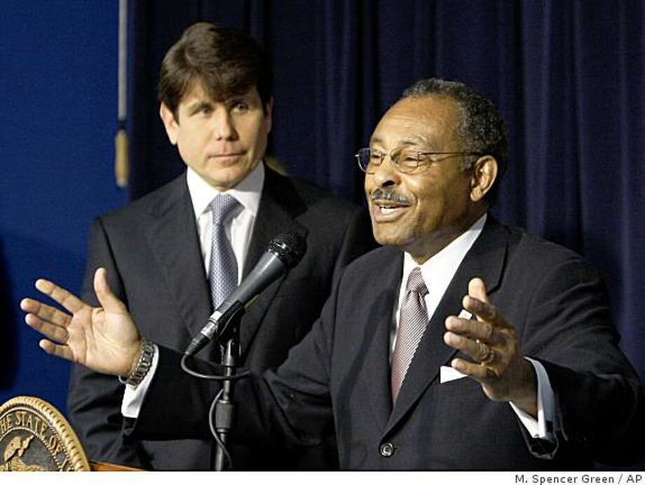 ** FILE ** Illinois Gov. Rod Blagojevich stands by as his choice to fill President-elect Barack Obama's U.S. Senate seat, former Ill. Attorney General Roland Burris addresses the media Tuesday, Dec. 30, 2008, in Chicago. Through numerous TV interviews and behind-the-scenes lobbying, Burris is campaigning hard for the Senate. (AP Photo/M. Spencer Green) Photo: M. Spencer Green, AP
