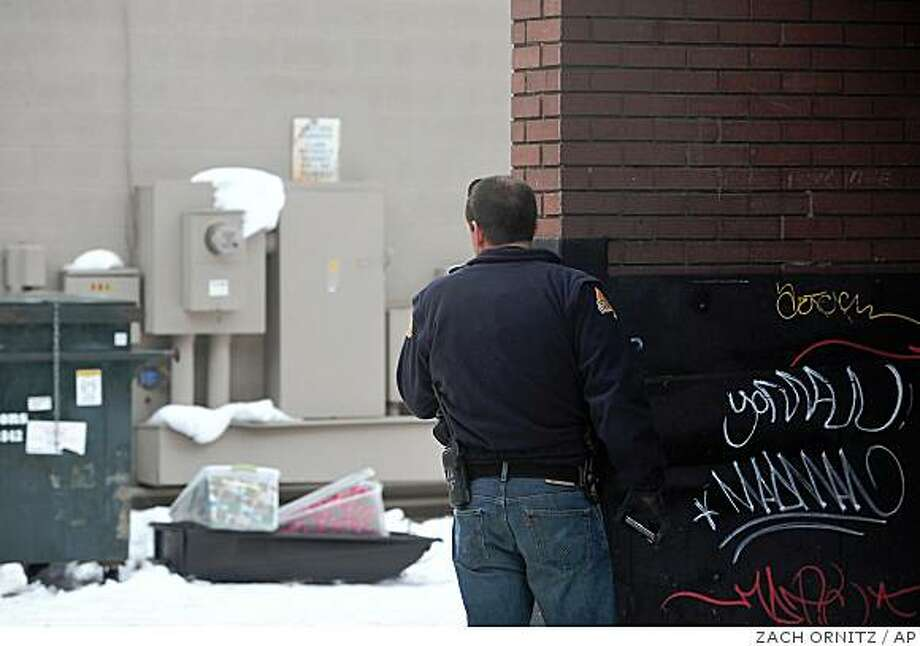 Aspen police officer Bill Linn pears from behind a wall at a sled containing wrapped packages left in an alleyway between Hopkins and Hyman Avenue in Downtown Aspen on Wednesday evening. Authorities recieved a tip alleging that explosives were placed in proximity of the Wells Fargo Aspen branch at 119 S. Mill St. and near the Vectra Bank Aspen branch at 534 E. Hyman Ave. Emergency responders shut down the downtown core to vehicles and set a large perimeter around several blocks.  (AP Photo/Zach Ornitz/Aspen Daily News) Photo: ZACH ORNITZ, AP
