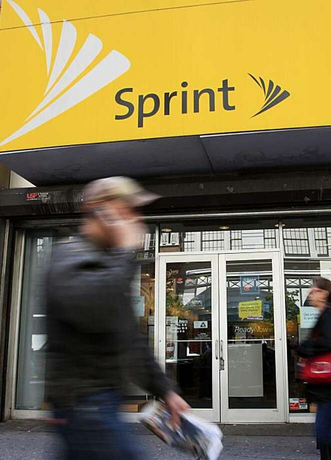 FILE - In this file photograph taken April 27, 2010, a man using a cell phone walks past a Sprint store, in New York. Sprint Nextel gained subscribers in its latest quarter, the first such gain in three years, as it continued to improve customer service and retention Wednesday, July 28,2010. Photo: Mark Lennihan, AP