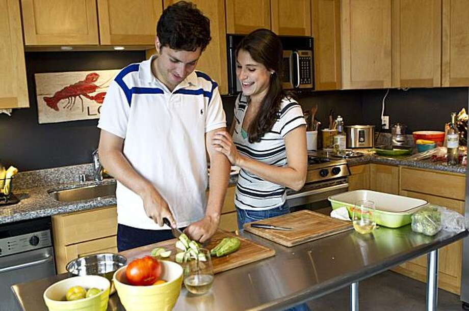 Sophie Brickman teaches her boyfriend Dave Eisenberg how to properly cut up vegetables at their apartment in San Francisco, Calif.  Brickman has been giving Eisenberg cooking lessons. Photo: Laura Morton, Special To The Chronicle