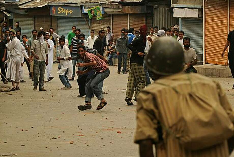 Kashmiri protestors throw stones against Indian police during anti Indian protest in downtown Srinagar on August 13, 2010. Four protesters were killed Friday when security forces opened fire during anti-India protests in Indian Kashmir, a day after the start of the Muslim fasting month of Ramadan, police said. The killings took the death toll from two months of violent protests in the Muslim-majority region to 55. The deaths came as influential separatist Mirwaiz Umar Farooq was freed from weeks of housearrest by authorities and led thousands of residents through  the main city, Srinagar, in a protest against Indian rule. Photo: Tauseef Mustafa, AFP/Getty Images