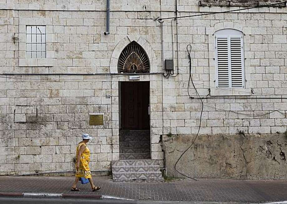 A woman walks in front of the family house of of Elias Abuelazam in the Arab-Jewish town of Ramle, central Israel, Friday, Aug. 13, 2010. Abuelazam, 33, was arrested Wednesday night in Atlanta before a flight to Israel, his native country, and charged with attempted murder in a July 27 knife strike in Flint that put the victim in a hospital for a week. Authorities said more charges were expected in Michigan, Ohio and Virginia. Photo: Dan Balilty, AP