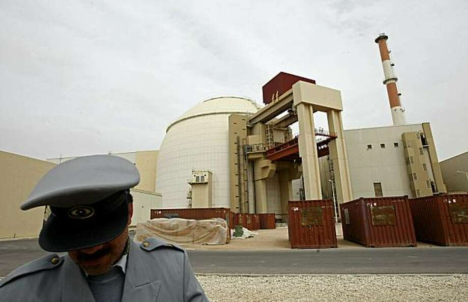 (FILES) An Iranian security guard stands in front of the building housing the reactor of the Bushehr nuclear power plant in the Iranian port town of Bushehr, 1200 kms south of Tehran, on February 25, 2009.  Iran will launch its first nuclear power plant next week, its atomic chief said on August 13, 2010, after years of delays to the highly sensitive project built by Russia in the southern city of Bushehr. Photo: Behrouz Mehri, AFP/Getty Images