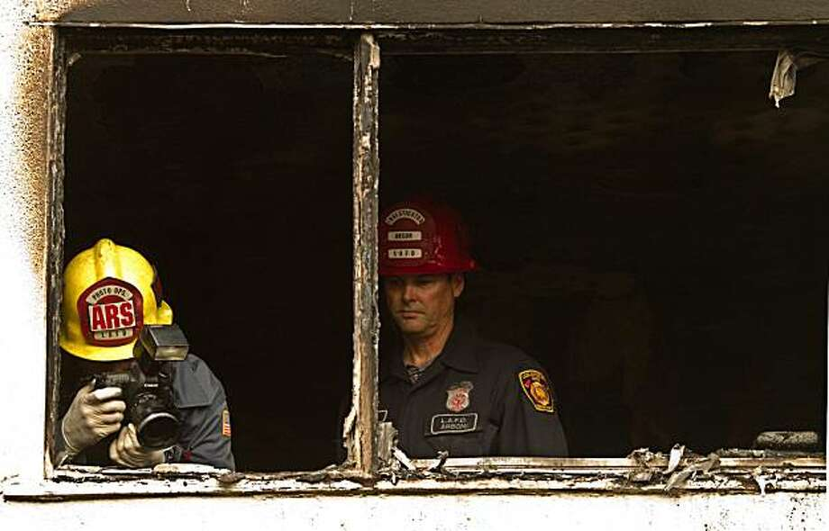 Arson investigators at the scene where two 15-year-old boys were found dead at an apartment complex  in Los Angeles on Thursday, Aug. 12, 2010.  . The pre-dawn fire in an apartment killed twin 15-year-old boys but their three siblings were rescued from the burning building, fire officials and relatives said. The teens' pregnant mother grabbed her 2-year-old son and escaped after the fire broke out at around 3:15 a.m. in the Crenshaw-area apartment, authorities said. Firefighters crawled on their bellies into the two-bedroom unit to rescue two girls, ages 5 and 7, fire Capt. Steve Ruda said. Crews doused the fire in about 20 minutes. The boys' names were not immediately released but a cousin identified them to the Los Angeles Times as Erick and Edward Ma Photo: Irfan Khan, AP
