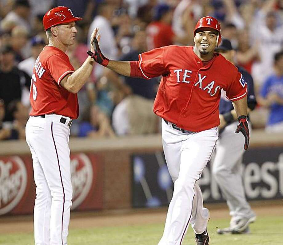 Nelson Cruz, right, of the Texas Rangers passes third base after hitting a game-winning home run in the 11th inning, slapping hands with coach Dave Anderson as the Rangers defeat the Boston Red Sox, 10-9, at Rangers Stadium in Arlington, Texas, on Friday, August 13, 2010. (Ron T. Ennis/Fort Worth Star-Telegram/MCT) Photo: Ron T. Ennis, MCT