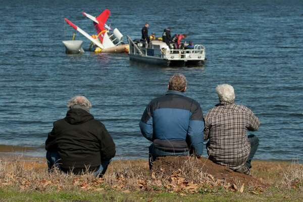 Residents of Areo Estates on Lake Palestine watch as the wreckage of a single-engine Varga is towed to the Deep End marina Friday, February 10, 2012 in Frankston, Texas.