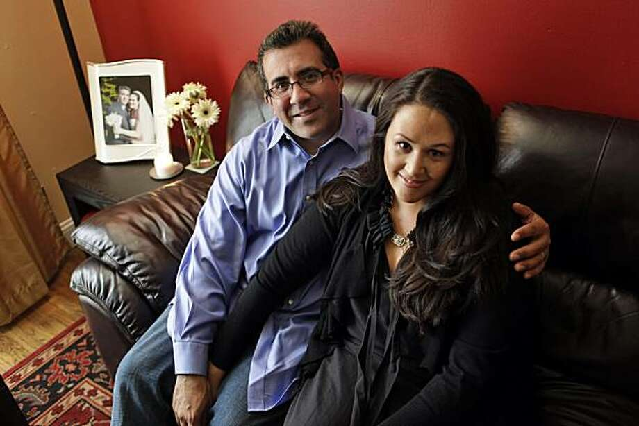 Sal Castaneda, 46, and Daragh Adamson, 36, met at the then-Pac Bell Park in 2000, when the Giants first got their new downtown digs. Daragh, who was working as an EMT at the park, spotted Castaneda, the radio and TV reporter who'd she listened to since high school. They dated for three years and married three months ago. They're seen here in their home in San Francisco, Calif., on Monday, August 2, 2010. Photo: Carlos Avila Gonzalez, The Chronicle