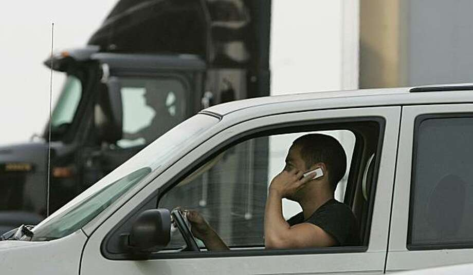 **ADVANCE FOR MONDAY, JUNE 30** A driver talks on his mobile phone while waiting in traffic at the Bay Bridge toll plaza in Oakland, Calif., Wednesday, June 25, 2008.  Chatty commuters and cell phone addicted motorists from San Diego to Crescent City face new restrictions starting July 1. Drivers over 18-years-old must use a hands-free device while talking. Drivers under 18 years-old will be prohibited from using phones unless making an emergency call to police, fire or medical authorities. (AP Photo/Jeff Chiu) Photo: Jeff Chiu, AP