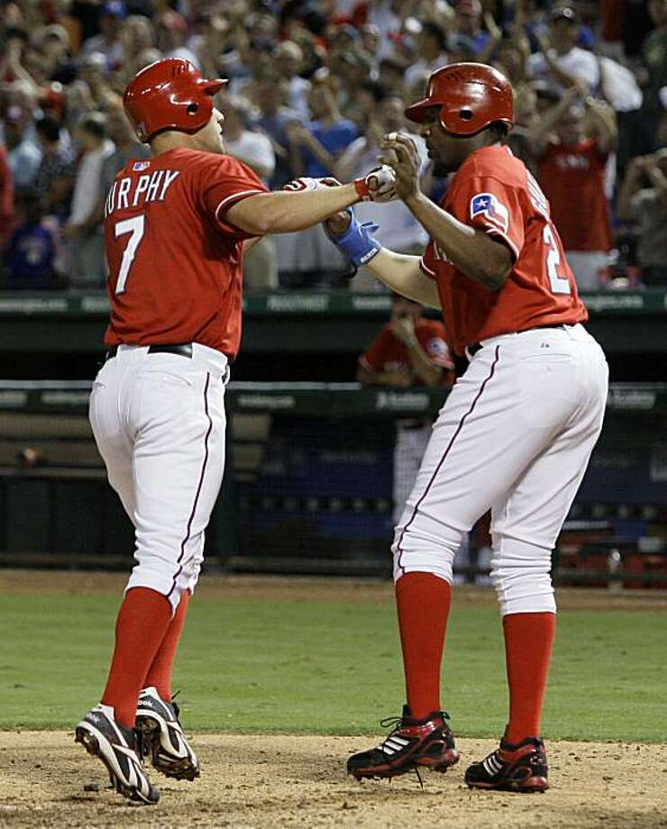 Texas Rangers' Vladimir Guerrero, right, congratulates David Murphy, left, after Murphy crossed home plate on his two-run home run off of New York Yankees' A.J. Burnett that scored Guerrero in the sixth inning of a baseball game Tuesday, Aug. 10, 2010, inArlington, Texas. Photo: Tony Gutierrez, AP