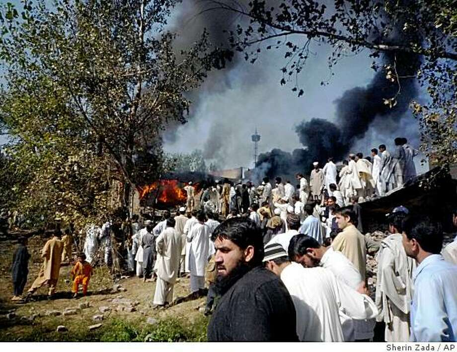 "In this Oct. 21, 2008 file photo, a World Food Program warehouse allegedly set fire by Pakistani Taliban militants burns, as a crowd gathers in Kanju in Pakistan's troubled Swat valley. Taliban militants are beheading and burning their way through the Swat Valley and now control most of the picturesque northwest region once dubbed ""the Switzerland of Pakistan,"" residents and officials say.(AP Photo/Sherin Zada, File) Photo: Sherin Zada, AP"