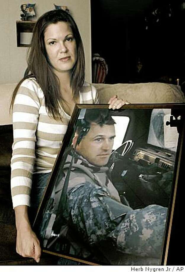 Amanda Henderson holds a photo of her late husband Sgt. 1st Class Patrick Henderson in her home in Henderson, Texas, Nov. 20, 2008. Patrick Henderson, afflicted by flashbacks and sleeplessness after a tour in Iraq, hanged himself in a shed behind his house as his wife and her son slept. (AP Photo/Herb Nygren Jr) Photo: Herb Nygren Jr, AP