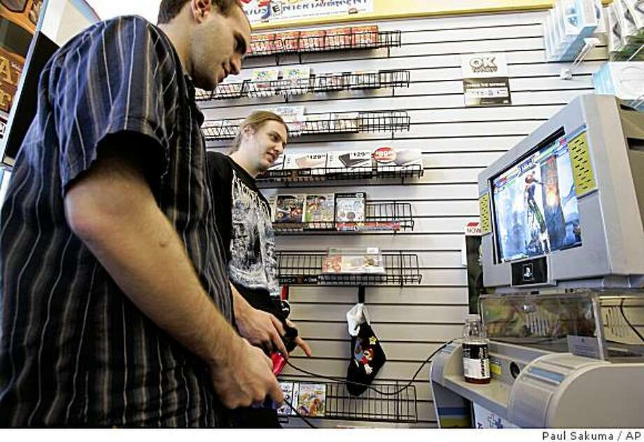 Customers play a game on a Playstation 2 at GameStop store in Redwood City, Calif., Wednesday, Dec. 17, 2008. Core gamers _ mostly young men who regularly, loyally buy new titles no matter how the economy is doing _ remain a crucial consumer base for companies trying to weather the downturn that's been evoking too many references to the Great Depression. Analysts say they will keep the industry afloat even as the rest of us cut back. (AP Photo/Paul Sakuma) Photo: Paul Sakuma, AP