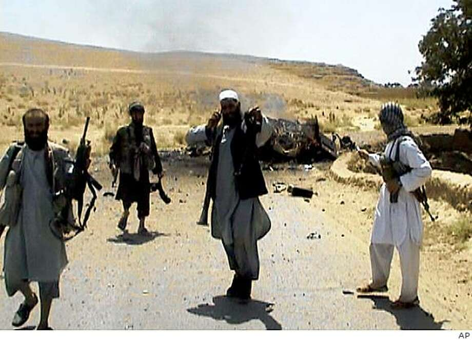 ** FILE ** This June 26, 2008 file frame grab from television footage reportedly shows Afghan militants holding weapons next to the burning wreckage of a vehicle in Wardak province, Afghanistan. Over the past year in Wardak province alone, Taliban fighters have taken over district centers, set up checkpoints on rural highways and captured Afghan soldiers. The Taliban in Wardak has its own governor and military chief, its own pseudo court system and its own religious leaders who act as judges. Bands of armed militants in beat-up trucks cruise the countryside, dispensing their own justice against accused spies and thieves. (AP Photo / APTN, File) ** TV OUT ** Photo: AP