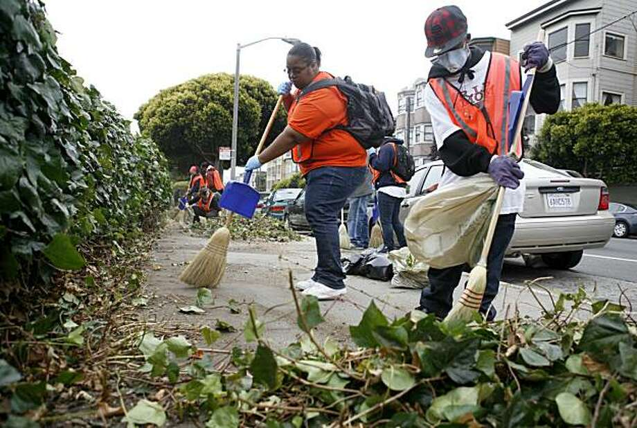Volunteers Teanna Tillery (background) and Jerome Shelton of the Community Clean Team brush cut shrubs and trash near the DMV office in San Francisco on Saturday. Photo: Jasna Hodzic, The Chronicle