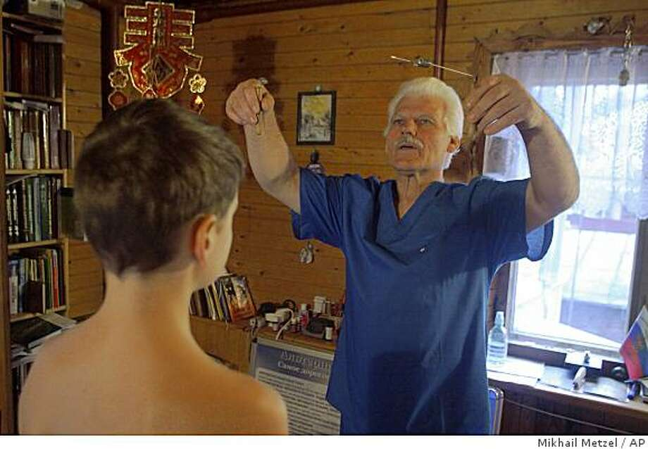 """Mikhail Fadkin, right, treats a boy named Sasha, who declined to give his last name, in the village of Malakhovka, 20 km ( about 13 miles) southeast of Moscow on Thursday, Dec. 11, 2008. The 63-year-old healer, claims he can cure a long list of disorders by putting his hands on a person's """"bio-energy field"""" and the Russian government has licensed him to do so. (AP Photo/ Mikhail Metzel) Photo: Mikhail Metzel, AP"""