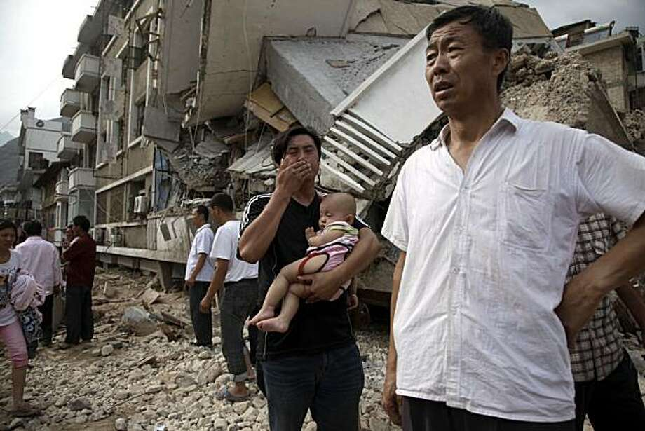 A Chinese man reacts as he carries a child near a building destroyed by a mud slide that swept through the town of Zhouqu in Gannan prefecture of northwestern China's Gansu province on Monday, Aug. 9, 2010. Rescuers dug through mud and wreckage Monday searching for 1,300 people missing after flash floods and landslides struck northwestern China. Photo: Ng Han Guan, AP