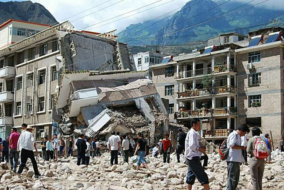 Chinese residents stand outside their damaged building in Zhouqu, northwest China's Gansu province on August 8, 2010, after a deadly flood-triggered landslide. At least 127 people were killed and nearly 2,000 missing after mudslides swept away homes and destroyed roads in northwestern China as the nation battled its worst flooding in a decade.     CHINA OUT Photo: Str, AFP/Getty Images