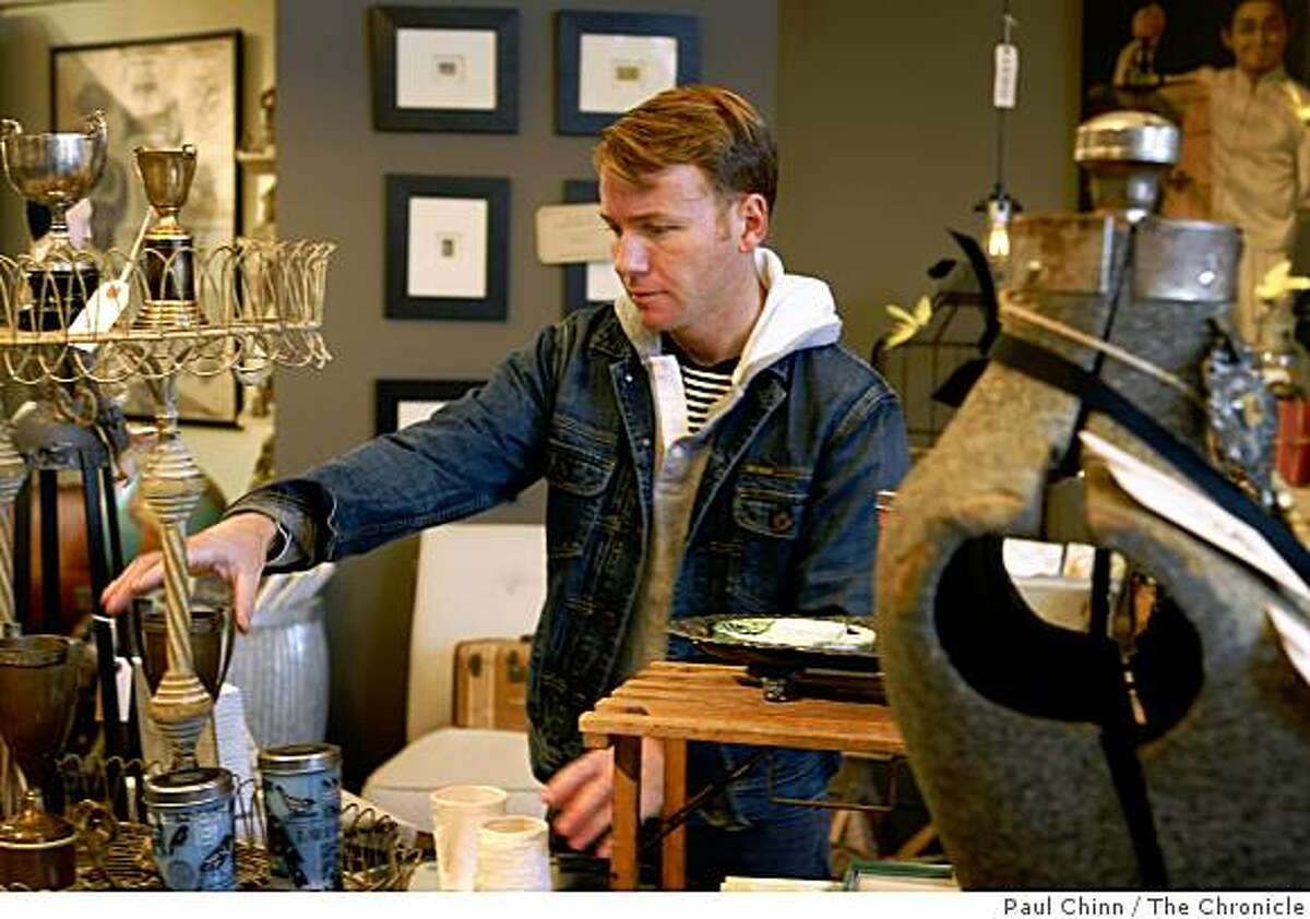 Paul Silvera arranges merchandise in his Scout home furnishing store in Oakland, Calif., on Friday, Dec. 19, 2008.