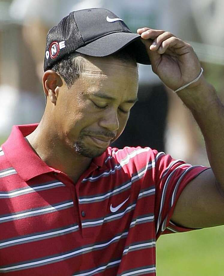 Tiger Woods tips his cap to the gallery as he walks to the 18th green during the fourth round of the Bridgestone Invitational golf tournament at Firestone Country Club in Akron, Ohio on Sunday, Aug. 8, 2010.  Woods finished the tournament at 18-over-par. Photo: Amy Sancetta, AP