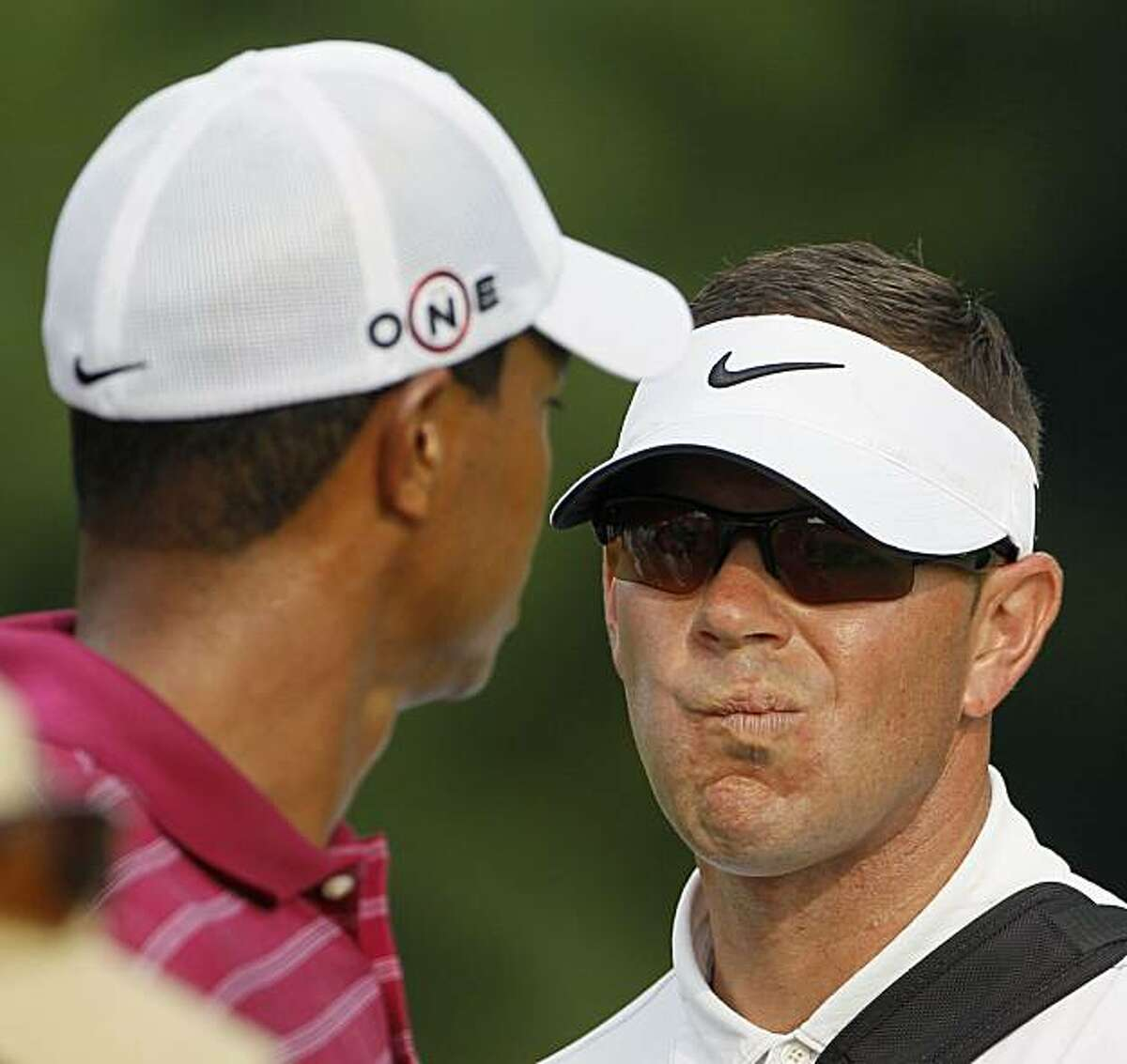 Coach Sean Foley, right, talks to Tiger Woods on the 10th tee during a practice round for the PGA Championship golf tournament Tuesday, Aug. 10, 2010, at Whistling Straits in Haven, Wis.