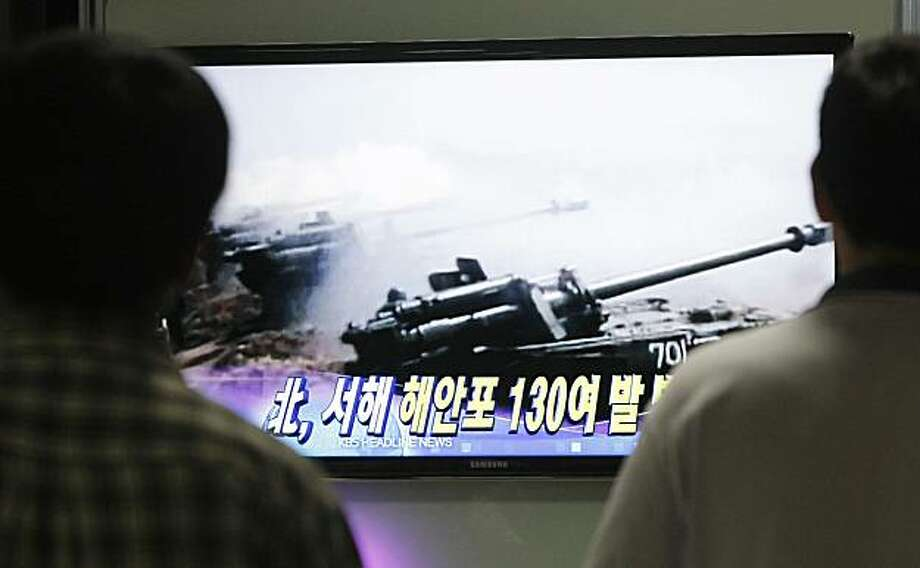 "South Koreans watch a TV program broadcasting a report about North Korea fired artillery off west coast, at Seoul train station in Seoul, South Korea, Monday, Aug. 9, 2010. North Korea fired about 110 rounds of artillery Monday near its disputed sea border with South Korea, the South's military said, amid high tension over the deadly sinking of a South Korean warship blamed on North Korea. The Korean caption on the screen read: ""North Korea fired about 130 rounds of artillery."" Photo: Ahn Young-joon, AP"