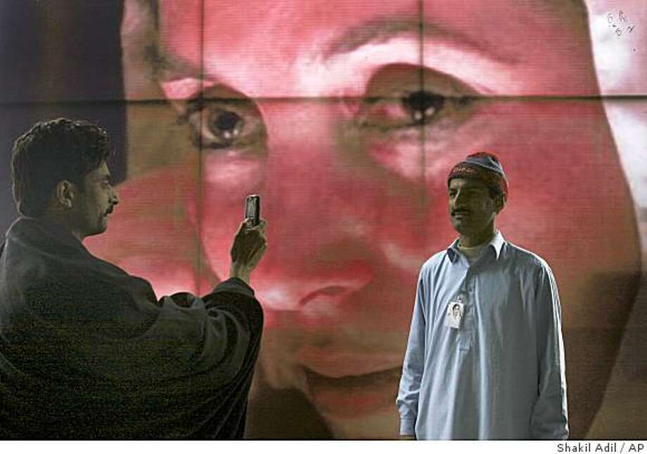 A man uses his mobile phone to take picture of his colleague in front of the poster of Pakistan's slain former Prime Minister Benazir Bhutto at her mausoleum, Saturday, Dec. 27, 2008 in Garhi Khuda Bakhsh, Pakistan. More than 150,000 Pakistanis flocked to the mausoleum of former Prime Minister Benazir Bhutto on Saturday after some walked hundreds of miles (kilometers) to offer flowers and kiss her grave on the first anniversary of her assassination. Some mourners beat their heads and chests and wailing. Several burst into tears. (AP Photo/Shakil Adil) Photo: Shakil Adil, AP