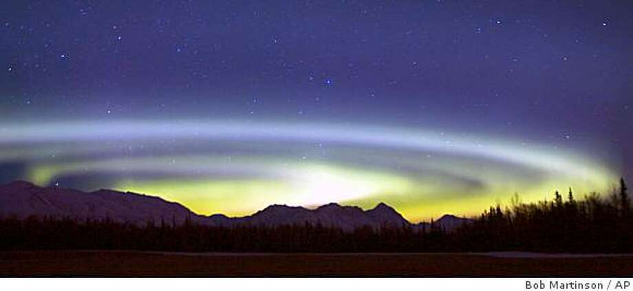 ** FILE ** In this Feb. 29, 2008 file photo the Aurora Borealis spins above the Talkeetna Range and a hay field on Farm Loop Road near Palmer, Alaska, on Feb. 29, 2008. The center of the circular corona, usually near Earth's north pole sometimes fluctuates further south and can be seen from a lower latitude as in this instance. (AP Photo/Bob Martinson, File) Photo: Bob Martinson, AP