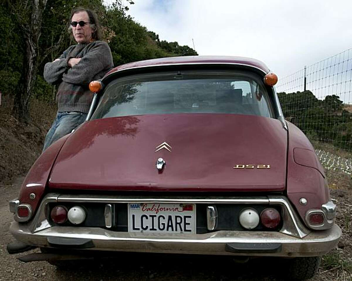 Randall Grahm of Bonny Doon Vineyard leans against his car which is adorned with the license plate LCIGARE in honor of one of one of his labels Le Cigare Volant, and is parked near one of his newest vineyards in San Juan Bautista, Calif., on Tuesday, July 27, 2010.