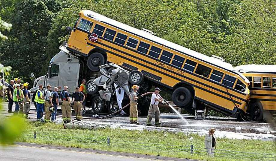 Emergency workers respond to an accident involving two school buses, a tractor trailer and a pickup truck, Thursday, Aug. 5, 2010, on eastbound Interstate 44 near Gray Summit, Mo. The school buses were carrying high school band students to an amusement park. Photo: J.B. Forbes, AP