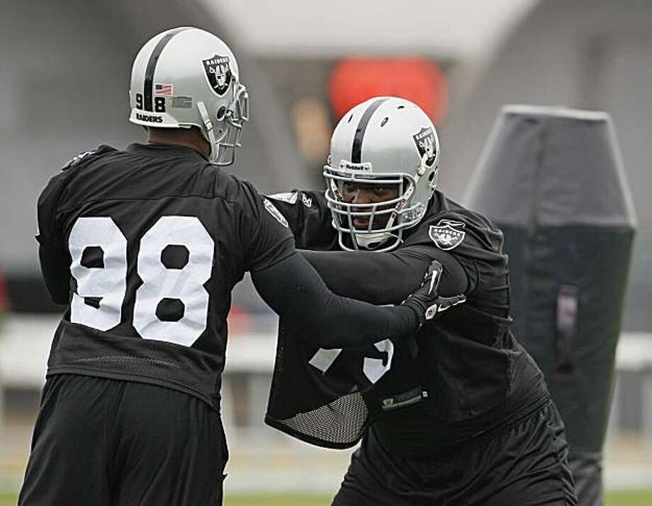 Oakland Raiders defensive end Jay Richardson, left, and defensive tackle John Henderson take part in a blocking drill during NFL football training camp in Napa, Calif., Friday, July 30, 2010. Photo: Eric Risberg, AP