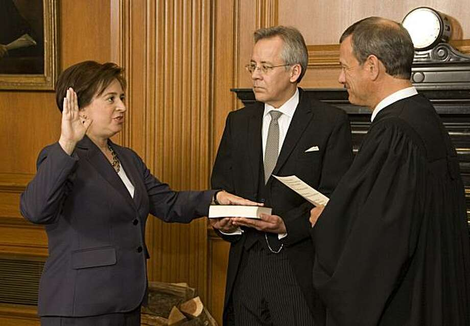 WASHINGTON - AUGUST 07:  In this handout image provided by the Collection of the Supreme Court of Justice, Chief Justice John G. Roberts, Jr., (R) administers the Judicial Oath to Elena Kagan (L) in the West Conference Room of the Supreme Court Building as Jeffrey P. Minear, (C) Counselor to the Chief Justice, holds the Bible August 7, 2010 in Washington, DC. Jeffrey P. Minear, Counselor to the Chief Justice, holds the Bible. Kagan, 50, who replaces retired Justice John Paul Stevens, becomes the fourth woman to sit on the high court, and is the first Supreme Court justice in nearly four decades with no previous experience as a judge. Photo: Handout, Getty Images
