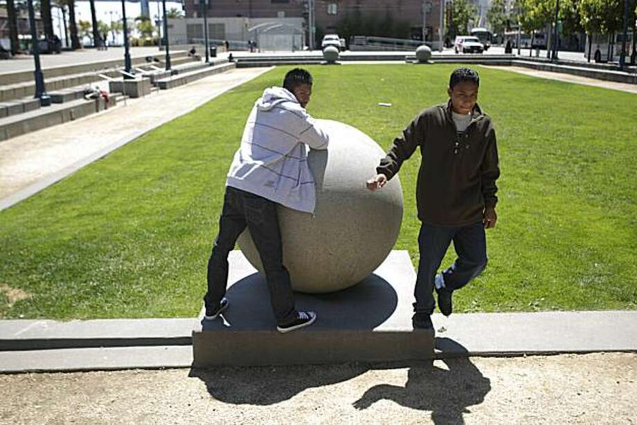 Luiz Ninos (right) hops off the base of a sculpture where he and Efren Gomez (left) both of Guatemala had been taking in the view from a sculpture on a patch of land at the south end of Justin Herman Plaza in San Francisco, Calif. on Friday August 6, 2010.   A proposal for two bocce ball courts to be built on a patch of land between Steuart Street and The Embarcadero at Justin Herman Plaza has been approved but critics are upset city officials didn't entertain other uses for the space before passing the proposal. Photo: Lea Suzuki, The Chronicle