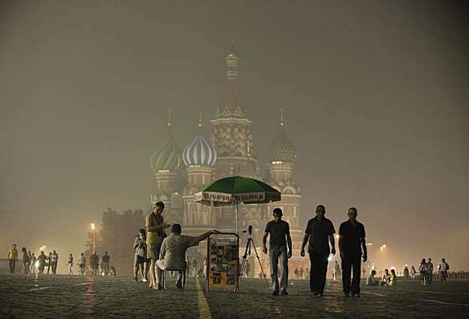 Moscow's St. Basil's Cathedral is seen through the heavy smog covering Moscow, Russia, late Friday, Aug. 6, 2010, as tourists walk past. Temperatures up to 100 F (38 C) have exacerbated forest and peat bog fires across Russia's central and western regions, destroying close to 2,000 homes. Photo: Alexander Zemlianichenko, AP