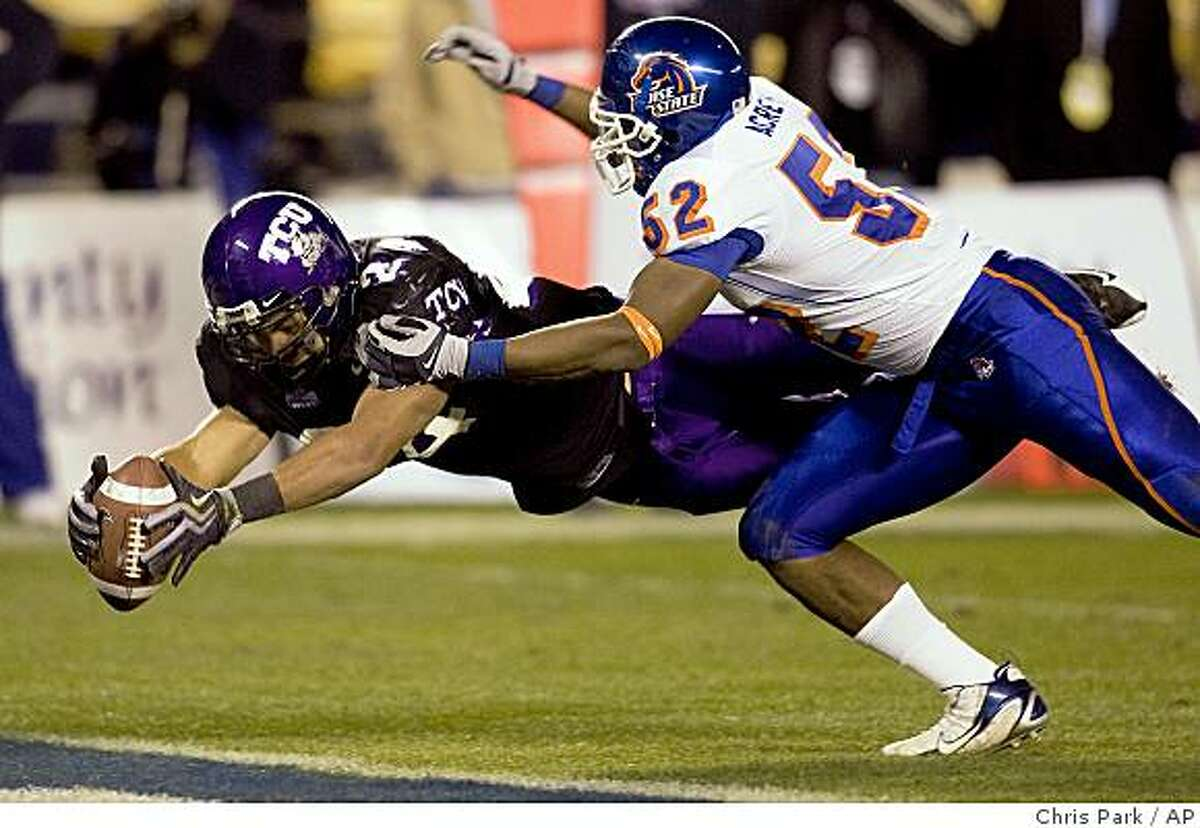 TCU's Joseph Turner, left, dives into the end zone on a 17-yard touchdown run while Boise State's Derell Acrey, right, defends during the second half of the Poinsettia Bowl NCAA college football game in San Diego on Tuesday, Dec. 23, 2008. TCU won 17-16. (AP Photo/Chris Park)