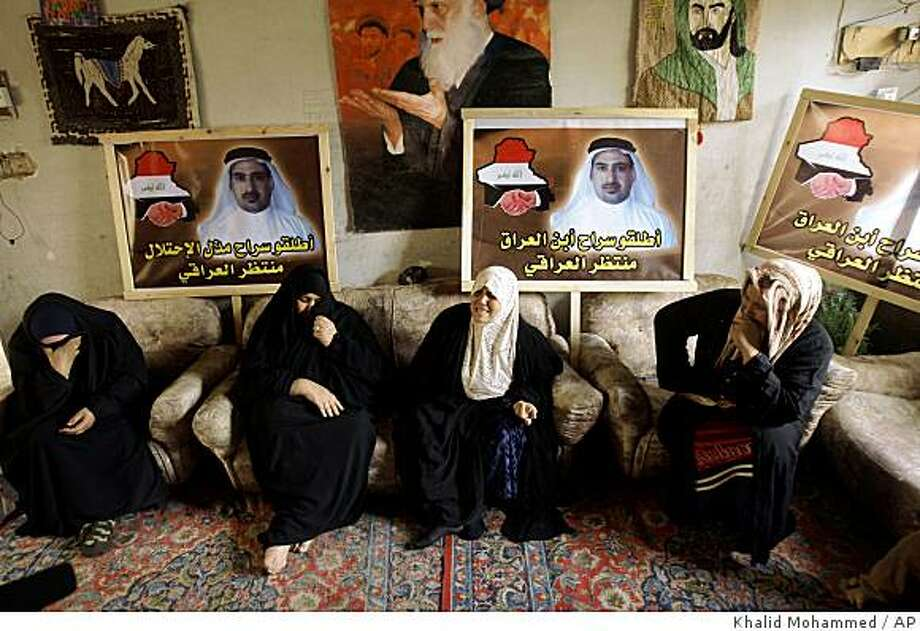 "Family members sit at the  home of Iraqi journalist Munthadar al-Zaidi. who threw his shoes at President George W. Bush, in Baghdad, Iraq, Monday, Dec. 22, 2008. The apology letter from the Iraqi journalist who threw his shoes at  Bush was written against his will after he was tortured in detention, his brother said Monday. Portraits show Munthadar with the text ""Release the son of Iraq, Munthadar al-Iraqi"". (AP Photo/Khalid Mohammed) Photo: Khalid Mohammed, AP"