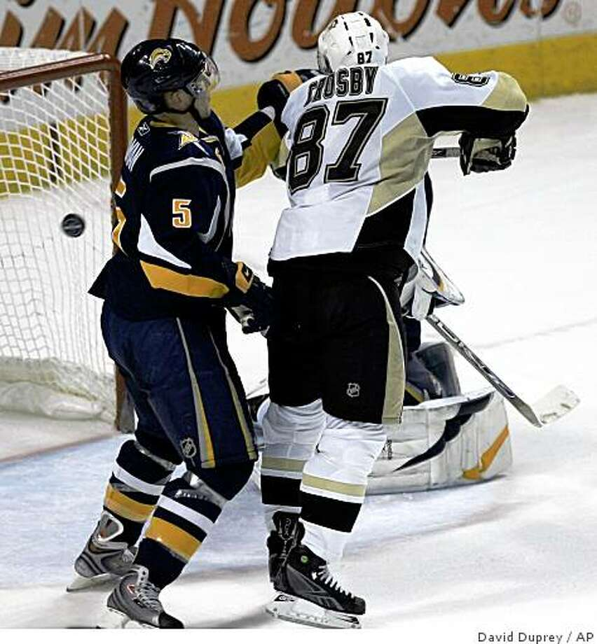 Pittsburgh Penguins' Sidney Crosby (87) scores the game-winning overtime goal under pressure from Buffalo Sabres' Toni Lydman (5) of Finland during the NHL hockey game at HSBC Arena in Buffalo, N.Y., Monday, Dec. 22, 2008. The Penguins won 4-3. (AP Photo/David Duprey) Photo: David Duprey, AP