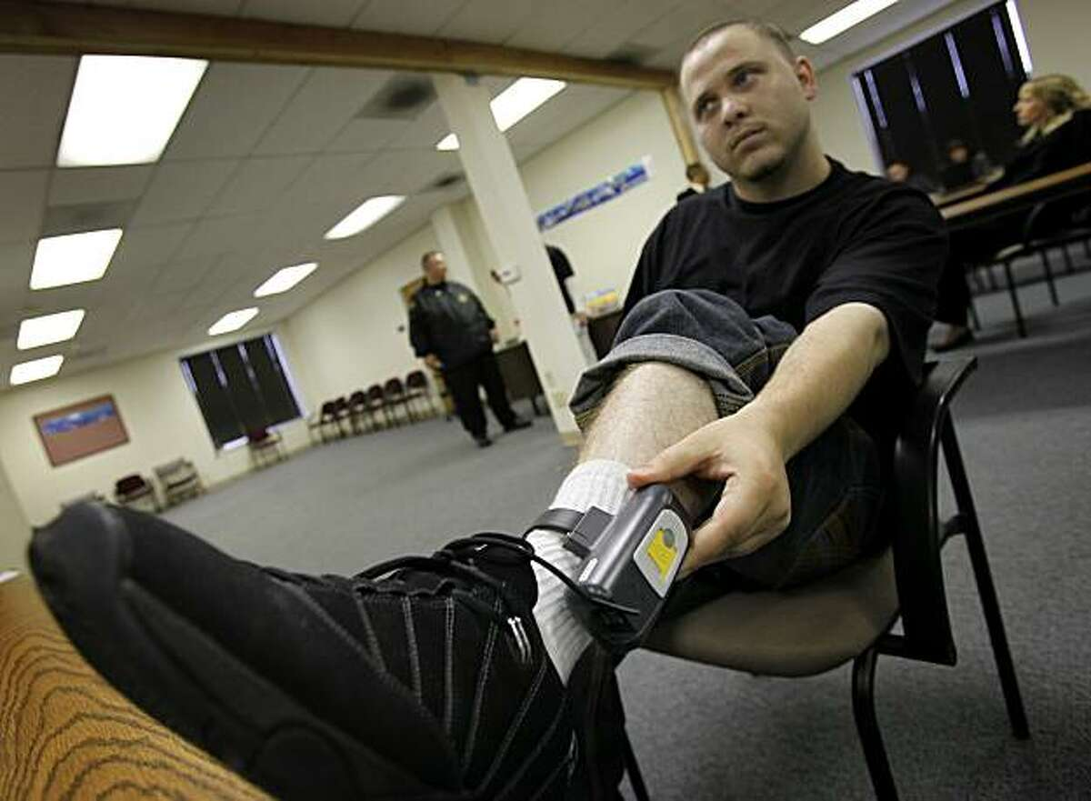 Former gang member Mark Morris adjusted his GPS anklet. East Bay parole agents conducted
