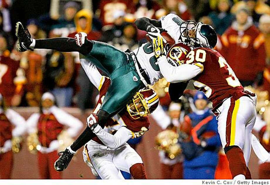 LANDOVER, MD - DECEMBER 21:  Receiver Reggie Brown #86 of the Philadelphia Eagles is stopped just short of the end zone by Fred Smoot #27 and LaRon Landry #30 of the Washington Redskins during the game on December 21, 2008 at FedEx Field in Landover, Maryland.  (Photo by Kevin C. Cox/Getty Images) Photo: Kevin C. Cox, Getty Images