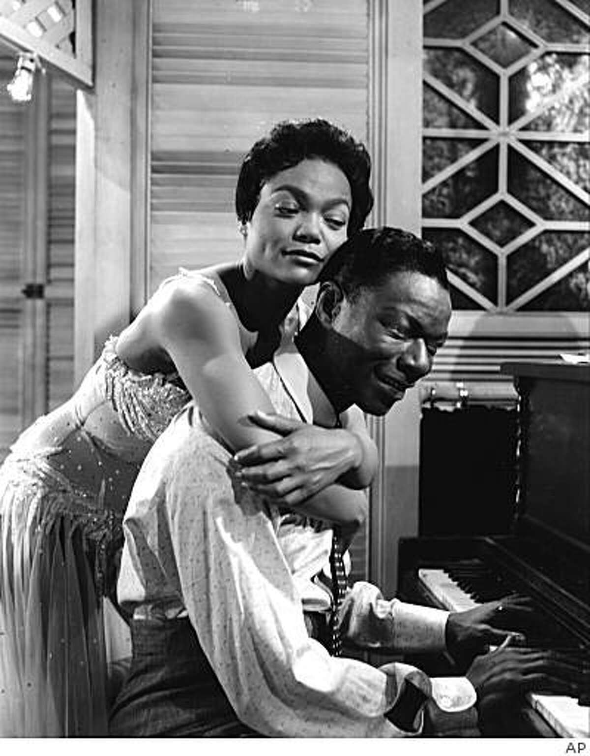 """In this undated file photo, Eartha Kitt hugs Nat King Cole, playing the piano in the role of W.C. Handy, in a scene from the 1958 movie """"St. Louis Blues."""" Kitt, a sultry singer, dancer and actress who rose from South Carolina cotton fields to become an international symbol of elegance and sensuality, died Thursday Dec. 25, 2008 of colon cancer. She was 81."""