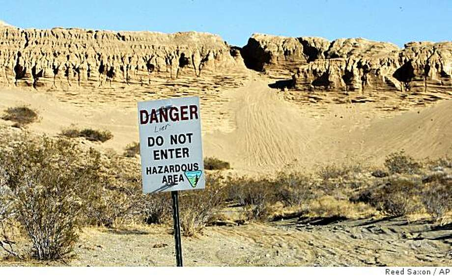 """The 150-foot high tailings from the Descarga Mill are carved by wind, rain and off-highway vehicle tracks, behind a fence and a sign with misspelled """"liar"""" graffiti added, near Randsburg, Calif., Jan. 18, 2008.  In the century since prospectors abandoned the mountains of tailings near beside this old desert mining camp, winds have carried away more than just handfuls of California history.  Soil samples have revealed arsenic levels thousands of times higher than what is considered acceptable. (AP Photo/Reed Saxon) Photo: Reed Saxon, AP"""