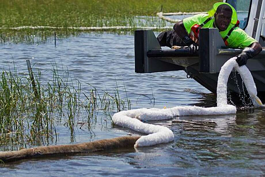 A worker replaces soiled absorbent boom with fresh boom while cleaning up oil from the Deepwater Horizon spill in the affected marshland of Terrebonne Parish Thursday, June 24, 2010, near Cocodrie, La. ( Smiley N. Pool / Houston Chronicle ) Photo: Smiley N. Pool, Chronicle