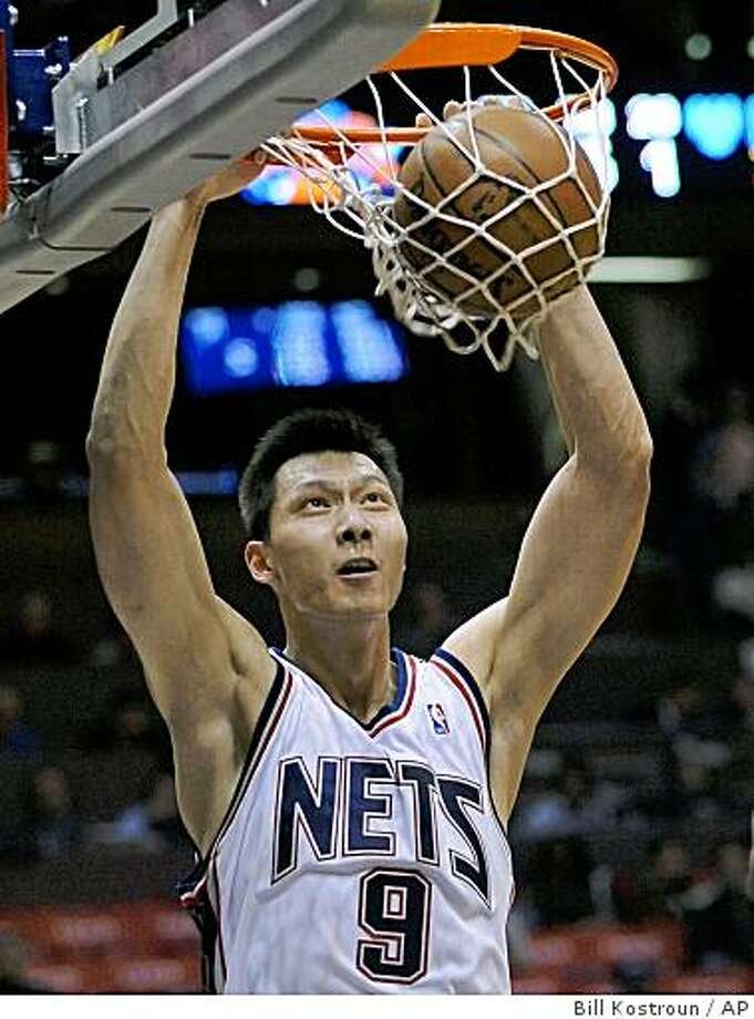 New Jersey Nets' Yi Jianlian dunks the ball during the first quarter of a game against the New York Knicks on Wednesday,  Dec. 10, 2008 in East Rutherford, N.J. Photo: Bill Kostroun, AP