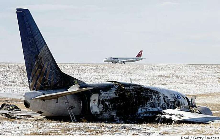 DENVER - DECEMBER 22:  As a Northwest Airlines jetliner lands on a nearby runway, the wreckage of a Continental Airlines jet sits in a ravine December 22, 2008 in Denver, Colorado. The plane veered off of the runway while trying to take off from Denver International Airport on the evening of December 20. (Photo by David Zalubowski-Pool/Getty Images) Photo: Pool, Getty Images